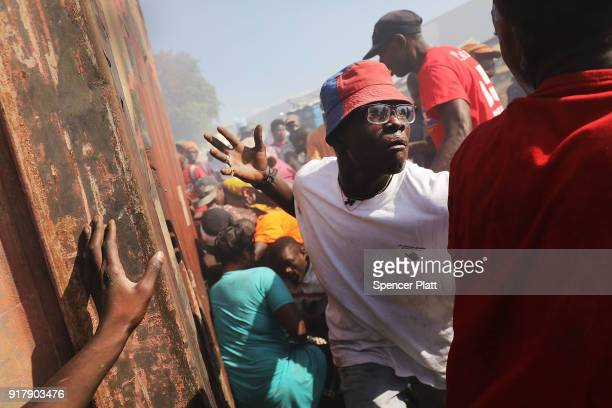 Haitians desperately try to get into a burning shipping container to salvage clothes during a fire at PortauPrince's historic Iron Market on February...