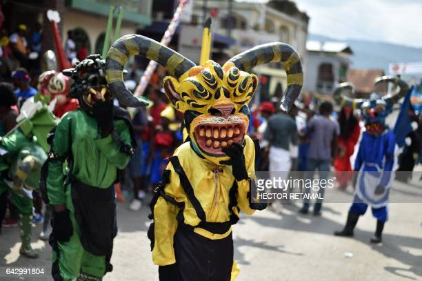 Haitians dressed in papier mache masks and costumes take part in the Carnival of Jacmel 95 km from PortauPrince February 19 2017 On the southern...