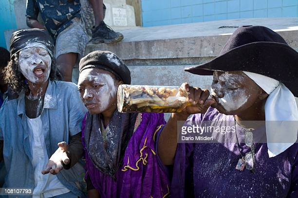 Haitians drink a hot pepperspiced homemade alcohol near the site of a cross dedicated to Baron Samedi in the National Cemetery of PortauPrince Haiti...