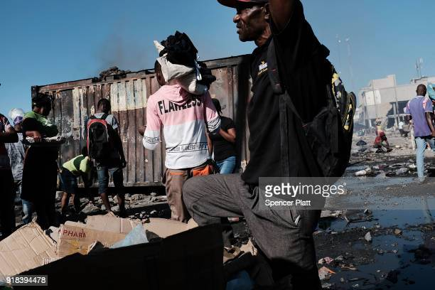 Haitians gather outside of PortauPrince's destroyed historic Iron Market after a fire yesterday on February 14 2018 in PortauPrince Haiti Hundreds of...