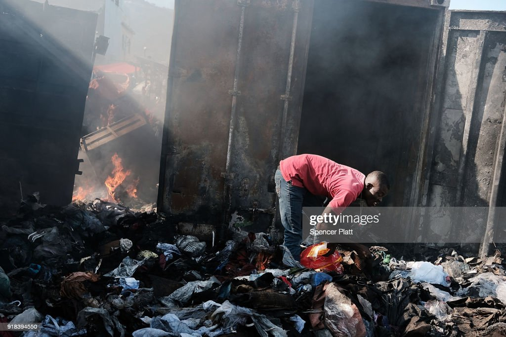 Haitians gather outside of Port-au-Prince's destroyed historic Iron Market after a fire yesterday on February 14, 2018 in Port-au-Prince, Haiti. Hundreds of locals vendors lost all of their merchandise in the early morning blaze which is still under investigation. Haiti, the poorest country in the Western Hemisphere, is still reeling from President Donald Trump's comments about the Caribbean nation and his decision to revoke Temporary Protected Status (TPS) for Haitians living in America following the 2010 earthquake that claimed over 300,000 lives. Haiti is currently preparing for the start of Carnival on Sunday.