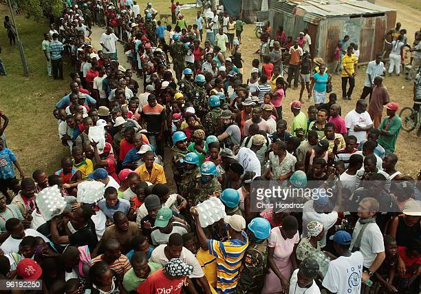 Haitians line up in an hourslong line to receive a case of water from aid groups while United Nations troops keep security January 26 2010 in Legoane...
