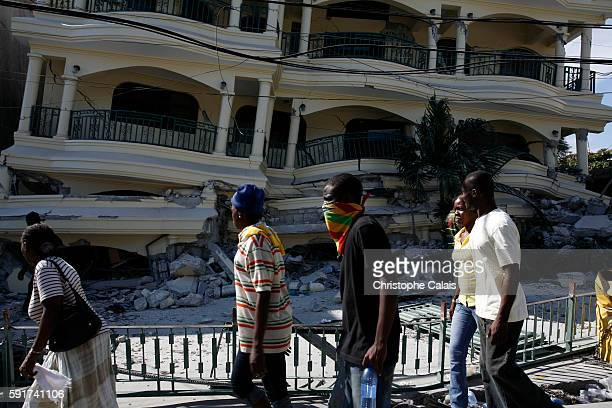 Haitians pass by the ruins of a destroyed building in PortauPrince two days after a magnitude 70 quake hit the impoverished island of Haiti on...