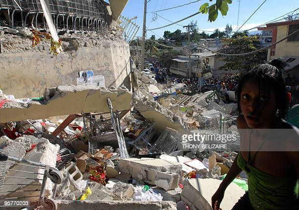 Haitians pass destroyed buildings on January 13 2010 in PortauPrince Haiti Planeloads of rescuers and relief supplies headed to Haiti Wednesday as...