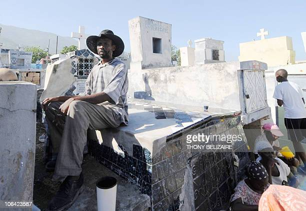Haitians pay homage at the grave of a relative on All Saints' Day at the municipal cemetery in Port-au-Prince, Haiti, on November 1, 2010. Haitians...
