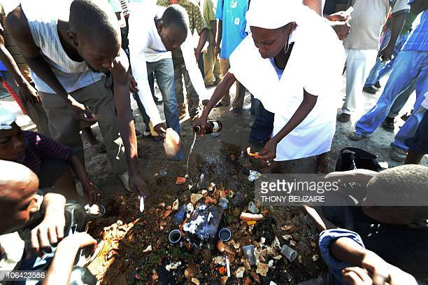 Haitians pay homage by offering food and drink on All Saints' Day at the municipal cemetery in Port-au-Prince, Haiti, on November 1, 2010. Haitians...