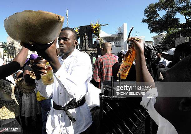 Haitians pay homage to relatives with food and drink on All Saints' Day at the municipal cemetery in Port-au-Prince, Haiti, on November 1, 2010....