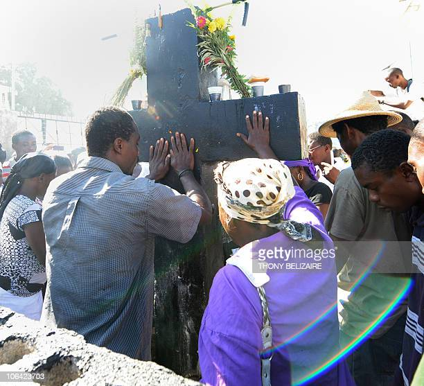 Haitians pay homage with food, and drink at the grave of Baron Samedi on All Saints' Day at the municipal cemetery in Port-au-Prince, Haiti, on...