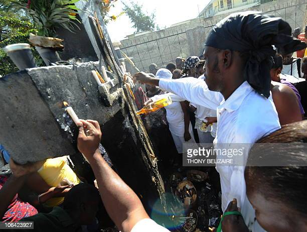 Haitians pay homage with food, drink and lit candles at the grave of Baron Samedi on All Saints' Day at the municipal cemetery in Port-au-Prince,...