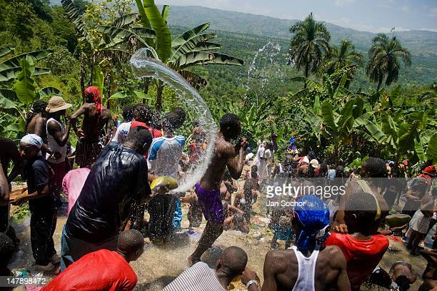 Haitians pilgrims play with water during the annual religious feast on July 16 2008 in Ville Bonheur Haiti Every year in summer thousands of pilgrims...