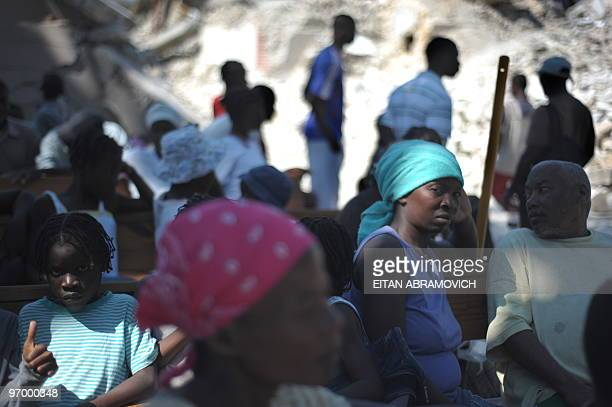 Haitians sit on benches that belonged to the devastated main church in the coastal city of Leogane on February 23 2010 The town of Leogane an hour...