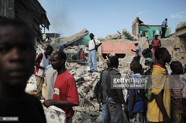 Haitians walk along a street in PortauPrince on January 27 2010 Desperate Haitians still faced a battle for survival as more than two weeks after a...