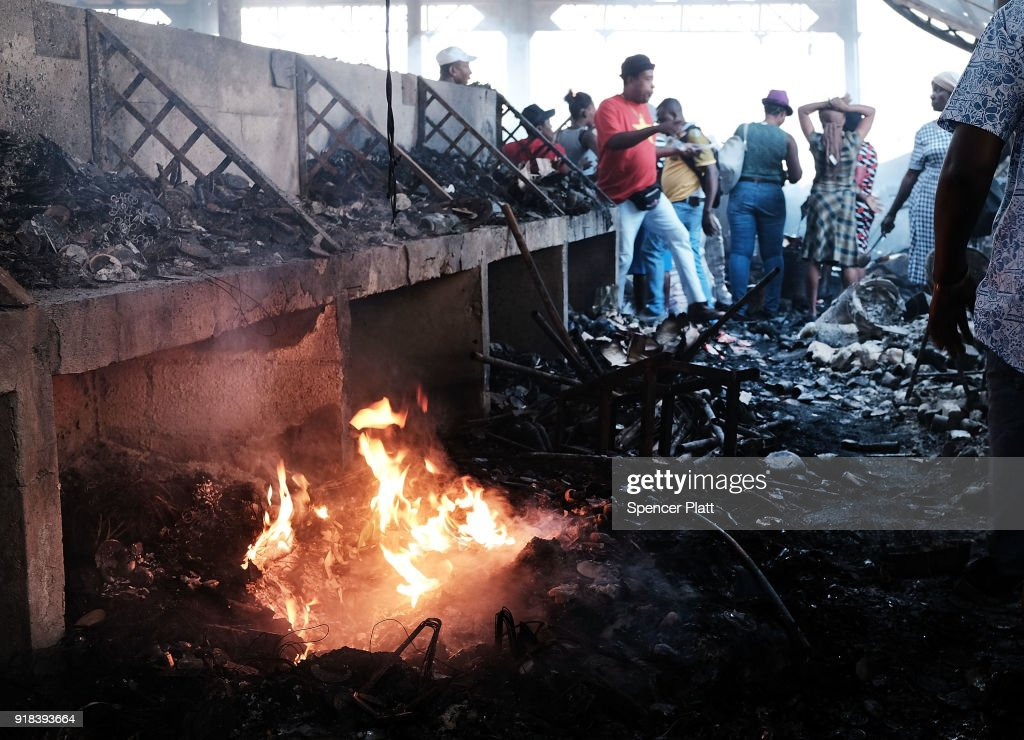 Haitians walk inside of Port-au-Prince's destroyed historic Iron Market after a fire yesterday on February 14, 2018 in Port-au-Prince, Haiti. Hundreds of locals vendors lost all of their merchandise in the early morning blaze which is still under investigation. Haiti, the poorest country in the Western Hemisphere, is still reeling from President Donald Trump's comments about the Caribbean nation and his decision to revoke Temporary Protected Status (TPS) for Haitians living in America following the 2010 earthquake that claimed over 300,000 lives. Haiti is currently preparing for the start of Carnival on Sunday.