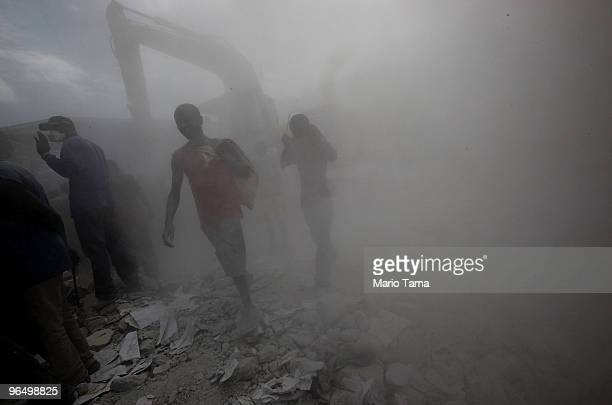Haitians walk through dust as they scavenge a site for materials February 8, 2010 in Port-au-Prince, Haiti. The death toll from the Jan. 12...