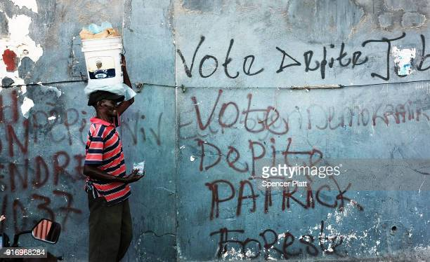 Haitians walk through Port au Prince as the city prepares for Carnival which is set to start later in the day on February 10 2018 in PortauPrince...