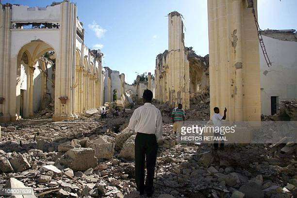 Haitians walks through the remains of the Notre Dame Cathedral on January 12, 2011 in Port-au-Prince at the one year anniversary of the quake of...