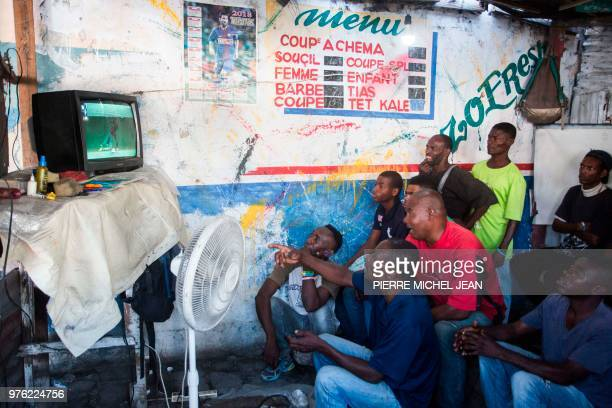 TOPSHOT Haitians watch the World Cup Group Stage match between Argentina and Iceland in a small hairdresser on the troittoir in downtown PortauPrince...