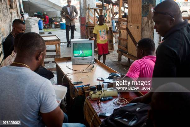Haitians watch the World Cup Group Stage match between Argentina and Iceland from a stand on the troittoir in downtown PortauPrince Haiti on June 16...