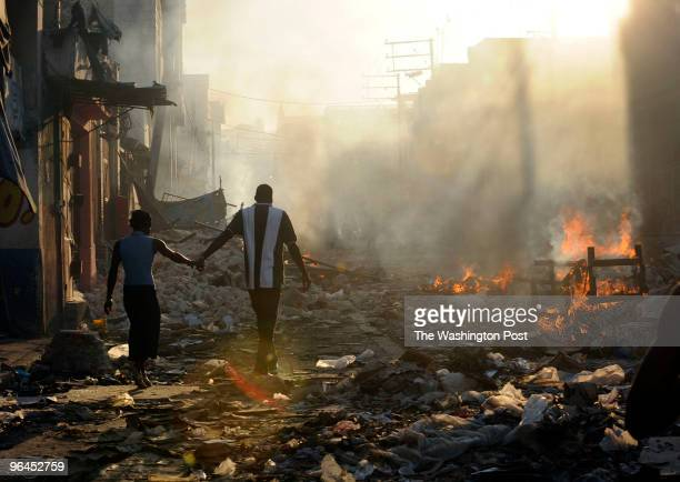 HaitiFire DATE January 18 2010 CREDIT Carol Guzy/The Washington Post via Getty Images LOCATION PortauPrince HAITI CAPTION A couple holds hands as...
