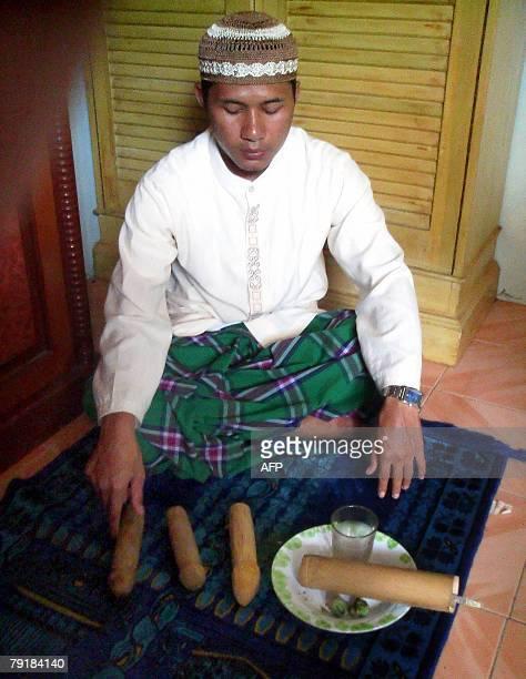 Haji Baban grandson of Indonesia's reknowned penis enlargement priestess Mak Erot offers phallus to clients visiting him at his home in Caringin near...