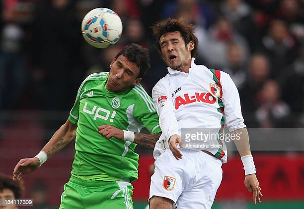 Hajime Hosogai of Augsburg heads for the ball with Mario Mandzukic of Wolfsburg during the Bundesliga match between FC Augsburg and VfL Wolfsburg at...