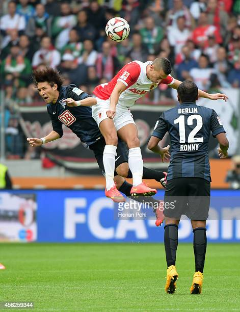 Hajime Hosogai of Hertha BSC and Nikola Djurdjic of FC Augsburg jump for a header during the game between FC Augsburg and Hertha BSC on September 28...