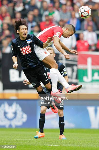 Hajime Hosogai of Hertha is fouled by Nikola Djurdjic of Augsburg during the Bundesliga match between FC Augsburg and Hertha BSC at SGL Arena on...