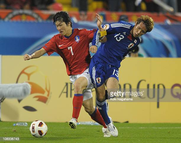 Hajime Hosogai of Japan and JiSung Park of South Korea compete for the ball during the AFC Asian Cup Semi Final match between Japan and South Korea...