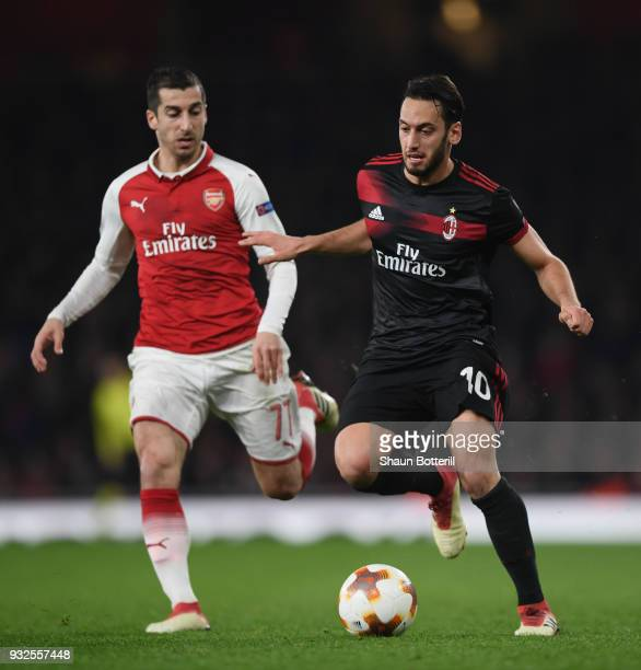 Haka Calhanoglu of AC Milan holds off a challenge from Henrikh Mkhitaryan of Arsenal during the UEFA Europa League Round of 16 second leg match...