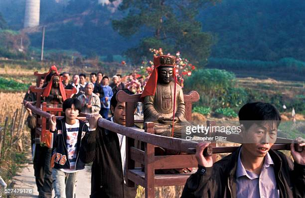 'Haka festival procession with Buddha weaving its way through village in a thunderous blaze of fireworks The festival which is called in Chinese...