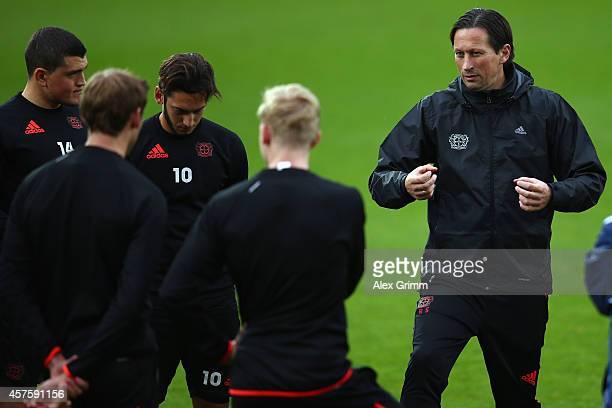 Hakan Calhanoglu listens as head coach Roger Schmidt talks during a Bayer Leverkusen training session ahead of their UEFA Champions League Group C...
