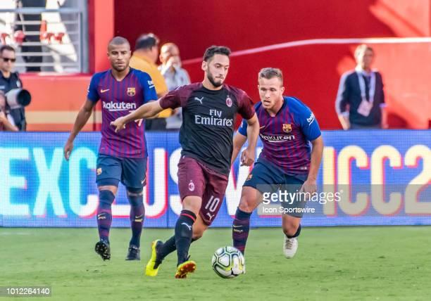 "Hakan Calhanoglu Midfielder, AC Milan shuttles the ball in front of Arthur Melo Midfielder, FC Barcelona and Rafael Alcantara ""Rafinha"" Midfielder,..."