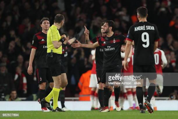 Hakan Calhanoglu of AC Milan argues with match referee Jonas Eriksson over the awarding of a penalty to Arsenal when it looked like there was on...