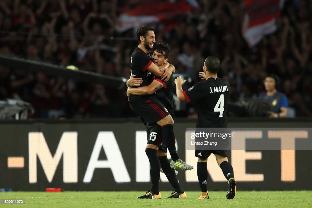 Hakan Calhanoglu of AC Milan celebrates a goal with teammate Jose Mauri and Gustavo Gomez during the 2017 International Champions Cup China match between FC Bayern and AC Milan at Universiade Sports Centre Stadium on July 22, 2017 in Shenzhen, China.