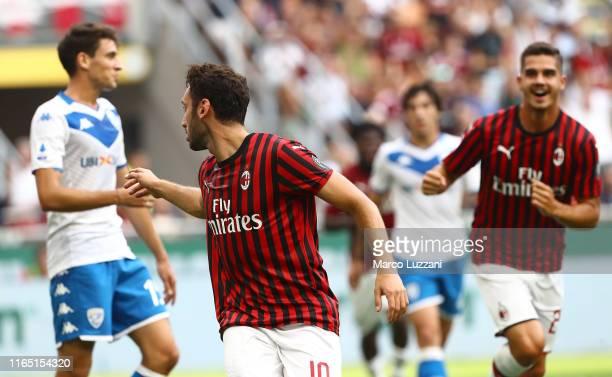 Hakan Calhanoglu of AC Milan celebrates after scoring the opening goal during the Serie A match between AC Milan and Brescia Calcio at Stadio...