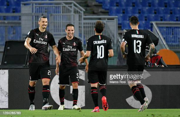 Hakan Calhanoglu of AC Milan celebrates after scoring the opening goal with teammates during the Serie A match between SS Lazio and AC Milan at...