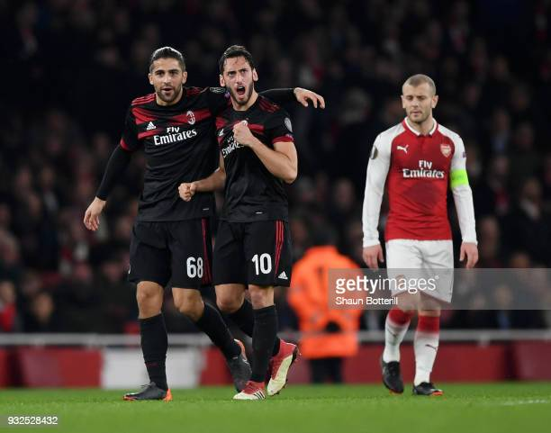 Hakan Calhanoglu of AC Milan clebrates the opening goal with Ricardo Rodriguez as Jack Wilshere of Arsenal looks on during the UEFA Europa League...