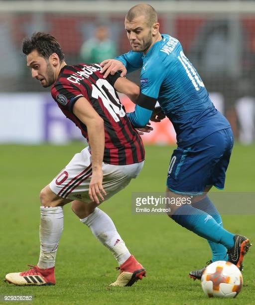 Hakan Calhanoglu of AC Milan competes for the ball with Jack Wilshere of Arsenal during UEFA Europa League Round of 16 match between AC Milan and...