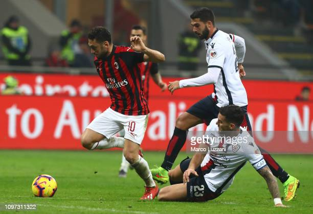 Hakan Calhanoglu of AC Milan competes for the ball with Luca Ceppitelli of Cagliari Calcio during the Serie A match between AC Milan and Cagliari at...