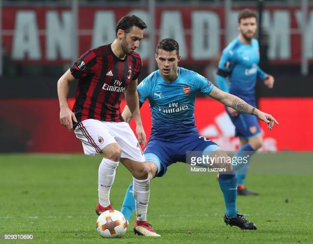 Hakan Calhanoglu of AC Milan competes for the ball withGranit Xhaka of Arsenal during UEFA Europa League Round of 16 match between AC Milan and...