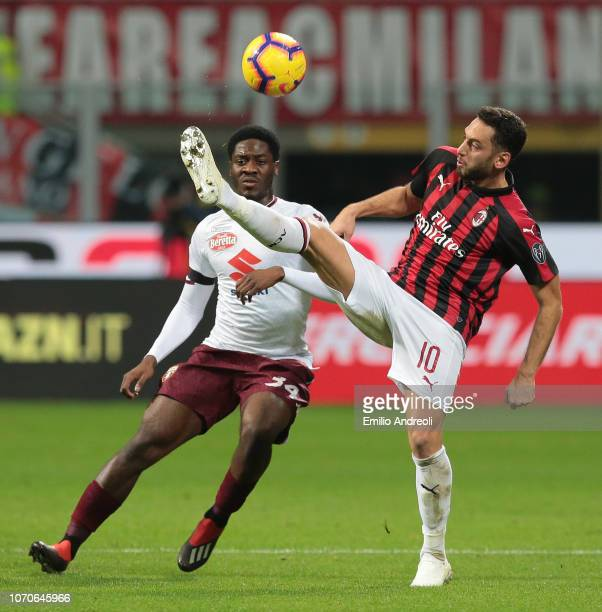 Hakan Calhanoglu of AC Milan controls the ball against Ola Aina of Torino FC during the Serie A match between AC Milan and Torino FC at Stadio...