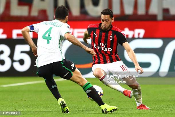 Hakan Calhanoglu of AC Milan is challenged by Francesco Magnanelli of US Sassuolo during the Serie A match between AC Milan and US Sassuolo at Stadio...
