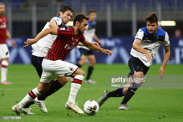 Hakan Calhanoglu of AC Milan is challenged by Marten De Roon of Atalanta BC during the Serie A match between AC Milan and Atalanta BC at Stadio...