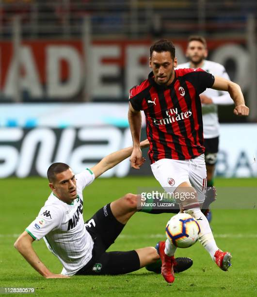 Hakan Calhanoglu of AC Milan is challenged by Merih Demiral of US Sassuolo during the Serie A match between AC Milan and US Sassuolo at Stadio...