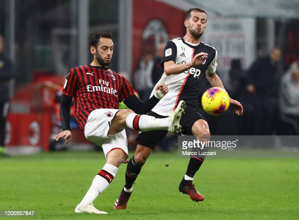 Hakan Calhanoglu of AC Milan is challenged by Miralem Pjanic of Juventus during the Coppa Italia Semi Final match between AC Milan and Juventus at...