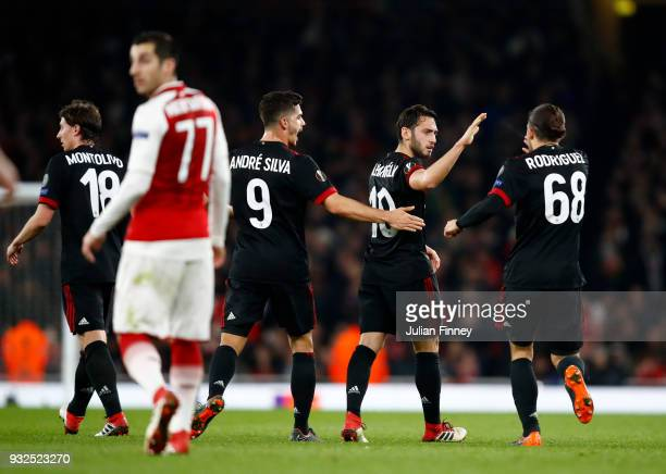 Hakan Calhanoglu of AC Milan is congratulated on scoring the opening goal during the UEFA Europa League Round of 16 Second Leg match between Arsenal...