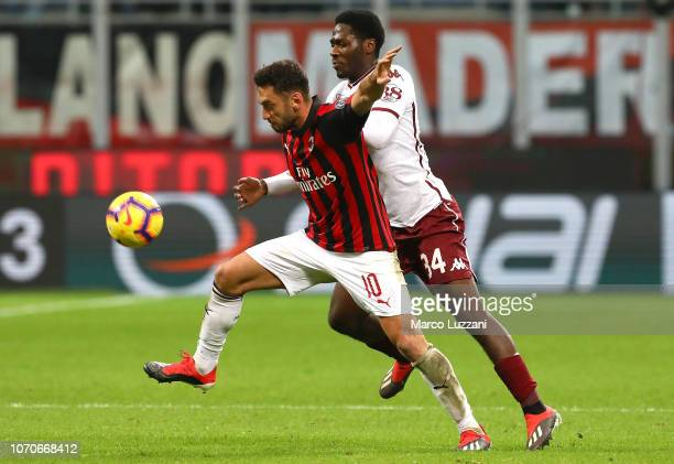 Hakan Calhanoglu of AC Milan s challenged by Ola Aina of Torino FC during the Serie A match between AC Milan and Torino FC at Stadio Giuseppe Meazza...