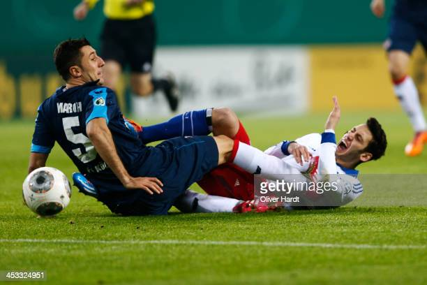 Hakan Calhanoglu of Hamburg and Dominic Maroh of Koeln compete for the ball during the DFP Cup round of 16 at Imtech Arena on December 3 2013 in...