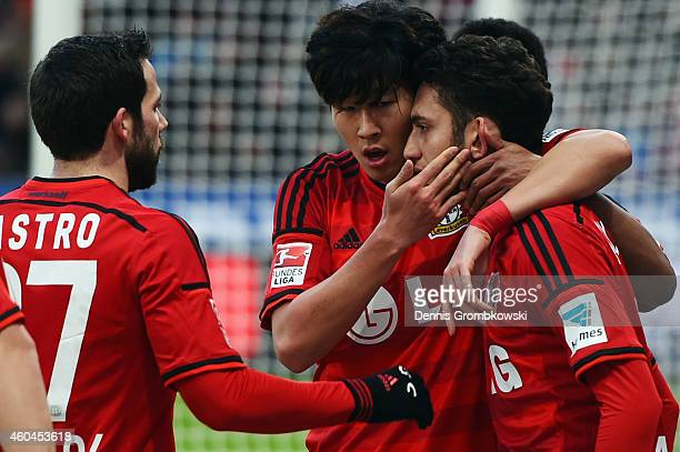 Hakan Calhanoglu of Leverkusen celebrates his team's first goal with team mates HeungMin Son and Gonzalo Castro during the Bundesliga match between...