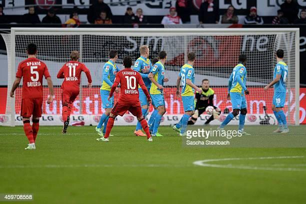 Hakan Calhanoglu of Leverkusen fires in a free kick towards the Koeln wall as goalkeeper Timo Horn of Koeln tries to save and Karim Bellarabi scores...